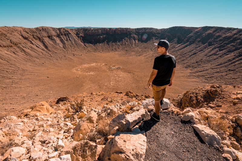 Man standing in front of giant crater